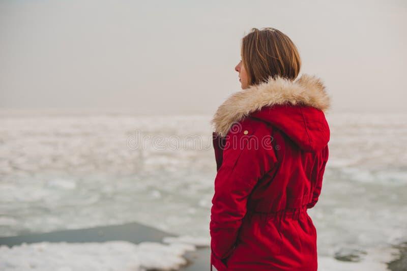 看冰冷的海的一件红色夹克的女孩 免版税库存照片