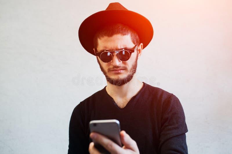 看冲击智能手机的哀伤的年轻人画象 免版税图库摄影