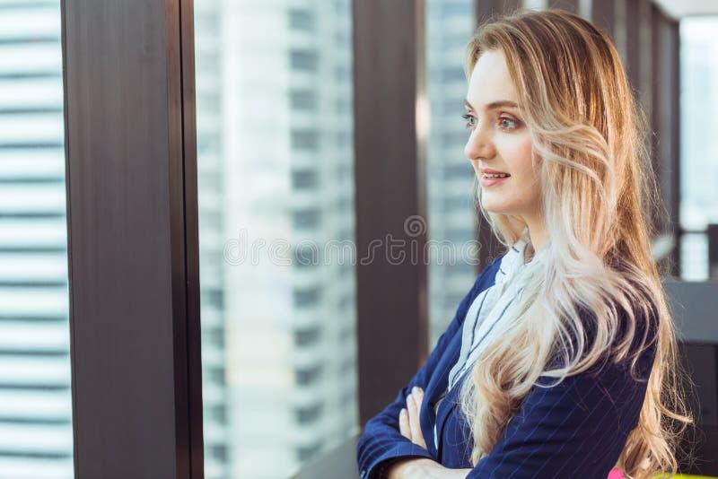看出于办公室窗口微笑的心情的白种人俄国女商人身分 免版税库存照片