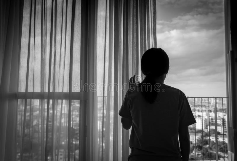 看出于窗口和认为的哀伤的成人亚裔妇女 被注重的和沮丧的少妇 有长的头发的绝望妇女 免版税库存图片