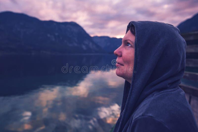 看剧烈的天空的孤独的妇女 免版税库存图片
