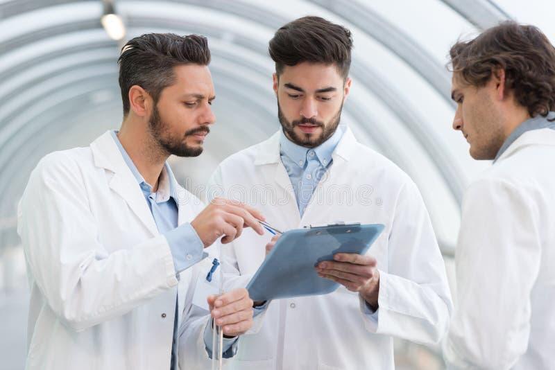 看剪贴板的labcoats的三个人 免版税库存照片