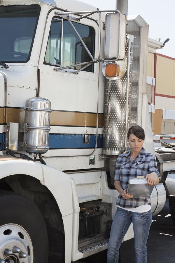 看剪贴板的妇女,当支持平板车卡车时 免版税库存照片