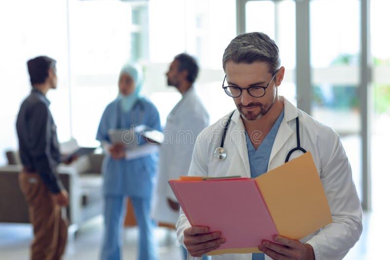 看医疗文件的男性医生在医院 免版税库存照片
