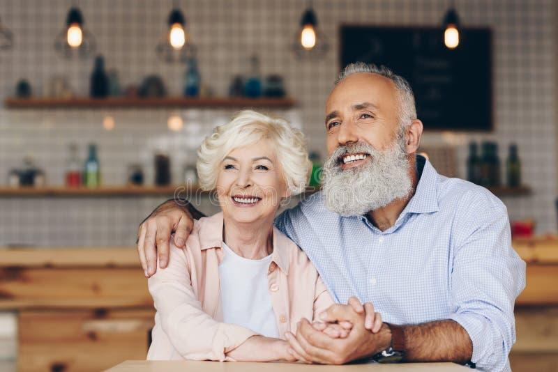 看去,当坐桌时的快乐的资深夫妇选择聚焦  免版税库存照片