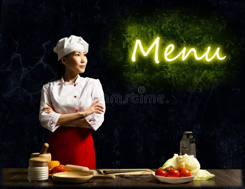 看发光的菜单的亚裔女性厨师 免版税库存照片