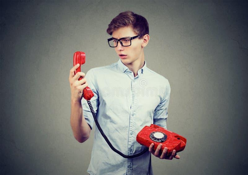 看古板的电话的迷茫的少年人 库存照片