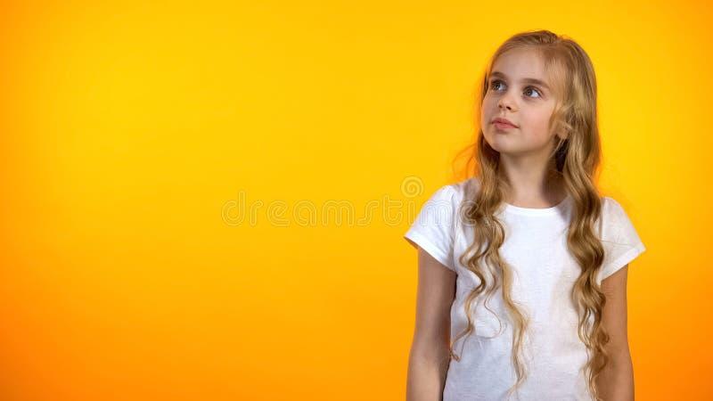 看可爱的十几岁的女孩在旁边隔绝在橙色背景,广告模板 免版税库存照片