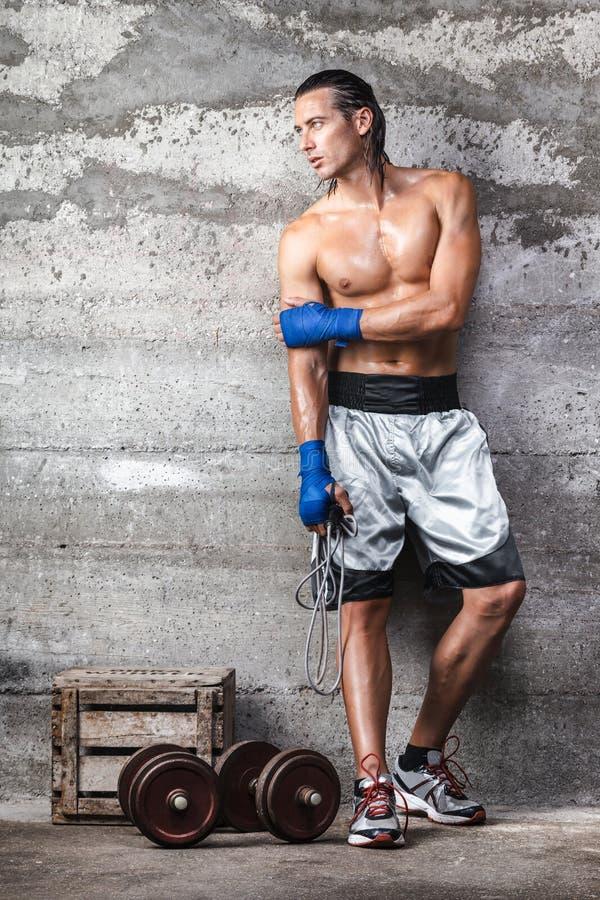 看可爱的拳击手的人站立在墙壁上和在旁边 免版税库存图片