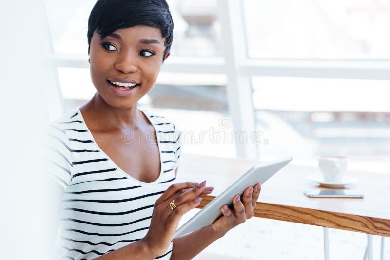 看可爱的美国黑人的女实业家拿着片剂计算机和  免版税库存照片