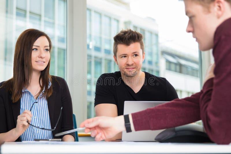 看同事的商人解释在书桌 免版税库存图片