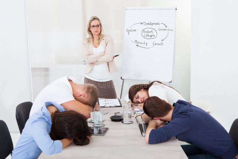 看同事的女实业家睡觉在介绍时 免版税库存图片
