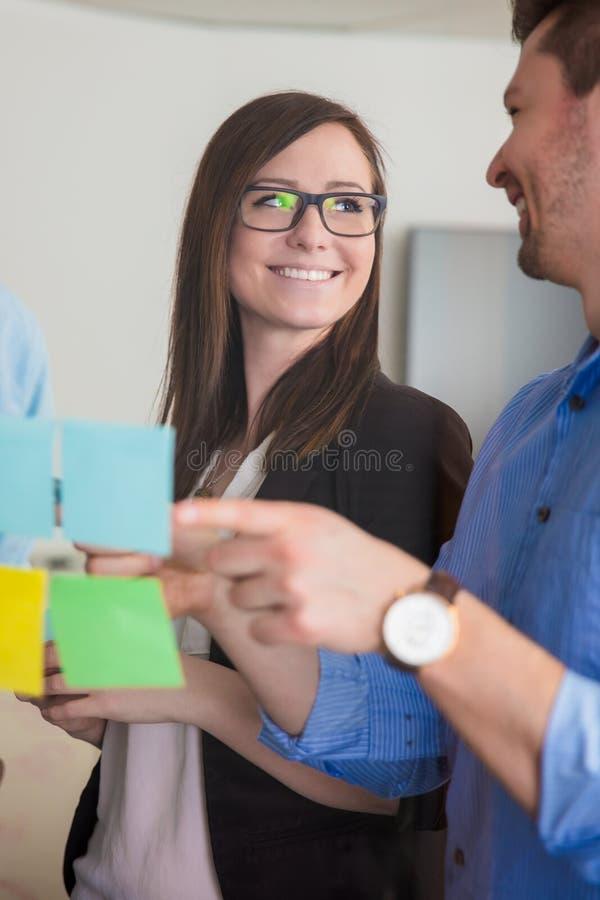 看同事的女实业家,当谈论在笔记O时 免版税库存照片