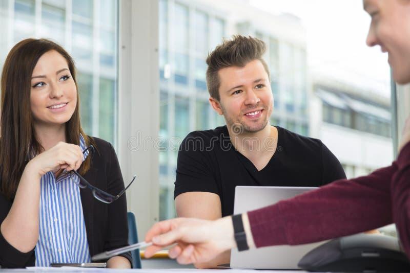 看同事的微笑的商人解释在书桌 图库摄影