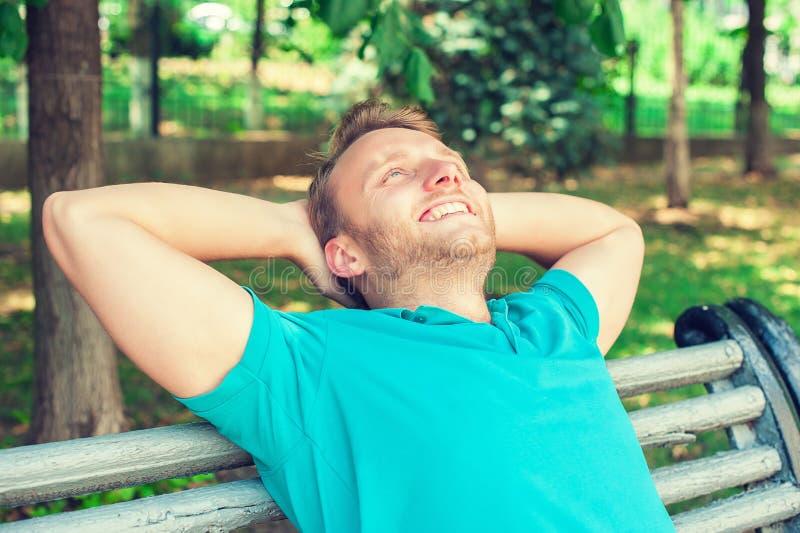 看向上在想法的衬衣的愉快的英俊的年轻人,放松在长凳 免版税库存照片