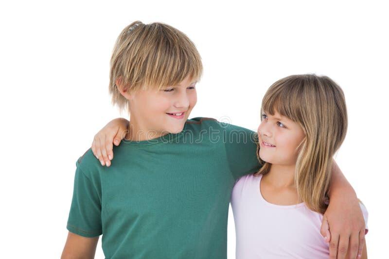 看和微笑的小男孩和女孩 免版税库存照片