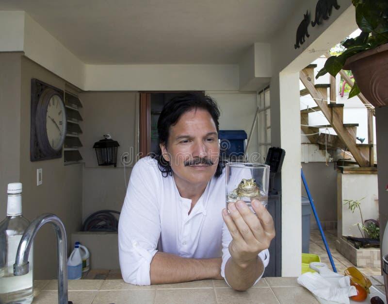 看和拿着杯与青蛙的水的西班牙mam 免版税图库摄影
