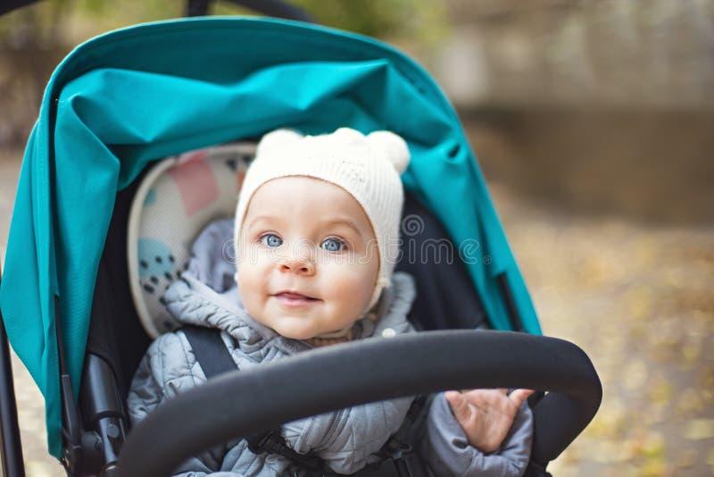 看和笑在公园的婴儿推车的愉快的可爱宝贝 图库摄影