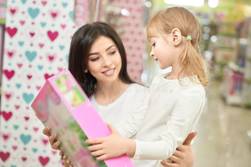 看和选择玩具的母亲和孩子在商店 图库摄影