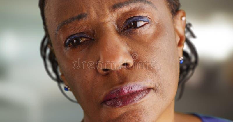 看哀伤地在距离的一个年长黑人妇女的特写镜头 免版税库存图片