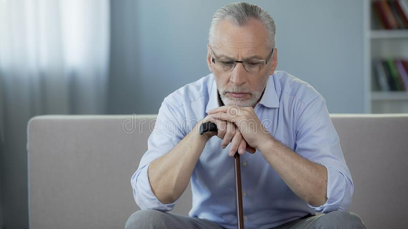 看哀伤的男性的领抚恤金者坐沙发,拿着走的框架和下来 库存图片