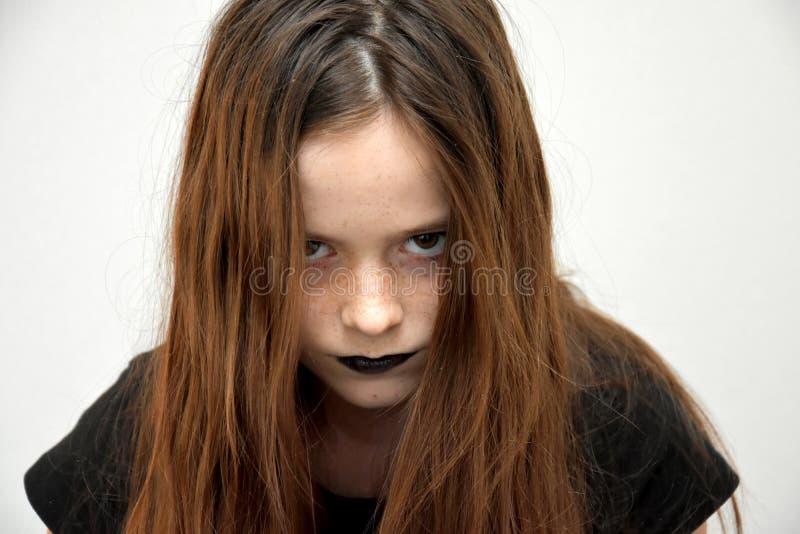 看哥特式的样式的十几岁的女孩非常恼怒 库存图片