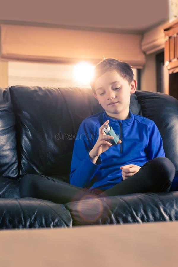 看哮喘吸入器的小男孩 免版税库存照片