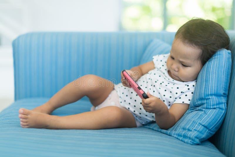 看在一个手机的小孩子很多电视 库存图片