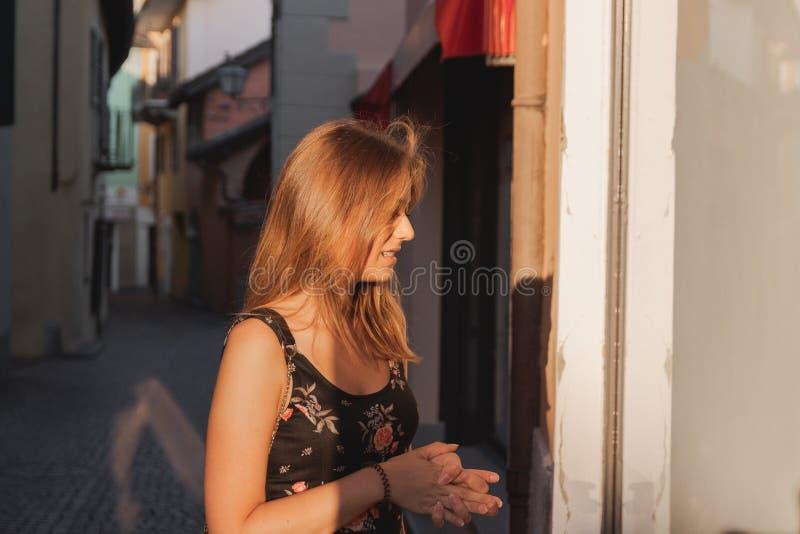 看在一个胡同的年轻困惑的妇女商店窗口在ascona 免版税库存照片