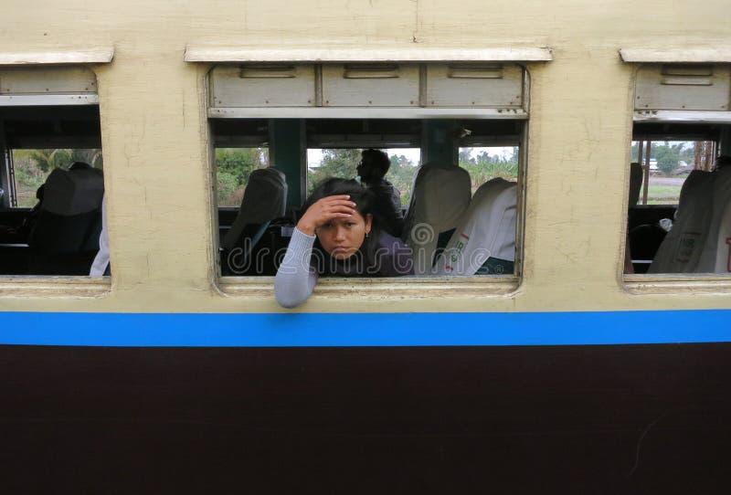 看在一列老火车的窗口的外面一个哀伤和疲乏的缅甸女孩 免版税库存照片