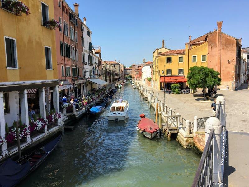 看在一条美丽的运河下的看法在威尼斯,意大利的心脏 当游人走,小船沿边靠码头 免版税库存照片