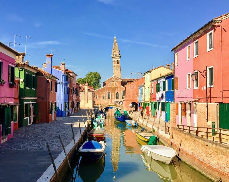 看在一条运河下的美丽的景色在Burano,意大利 房子是全部不同的颜色,并且运河小船有很多 免版税库存照片