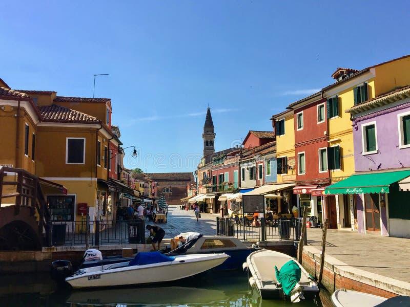 看在一条运河下的美丽的景色在Burano,有斜塔的意大利在背景中 免版税库存照片