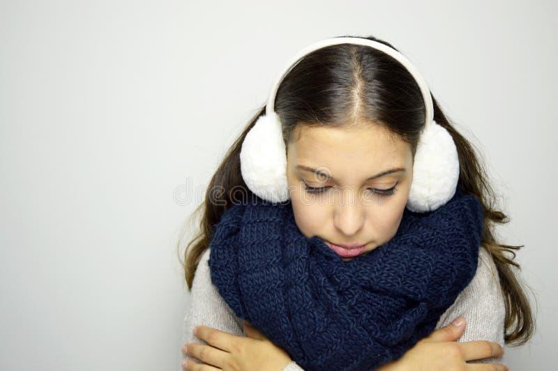 看在与流感或寒冷的不适下的发抖的少妇 是的少妇冷的佩带的御寒耳罩、scraf和毛线衣 复制空间 库存图片