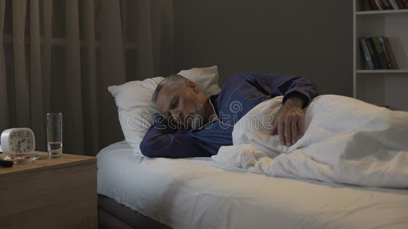 看在他的梦想的退休的人恶梦,睡觉在老人院病区里  免版税库存照片