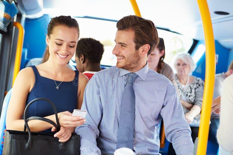 看在公共汽车的商人和妇女手机 免版税图库摄影