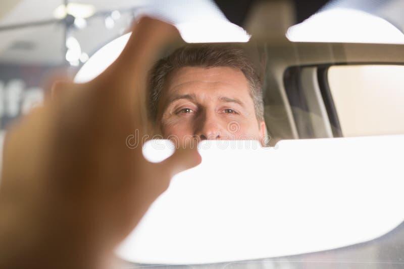 看在内部汽车镜子的人 免版税库存照片