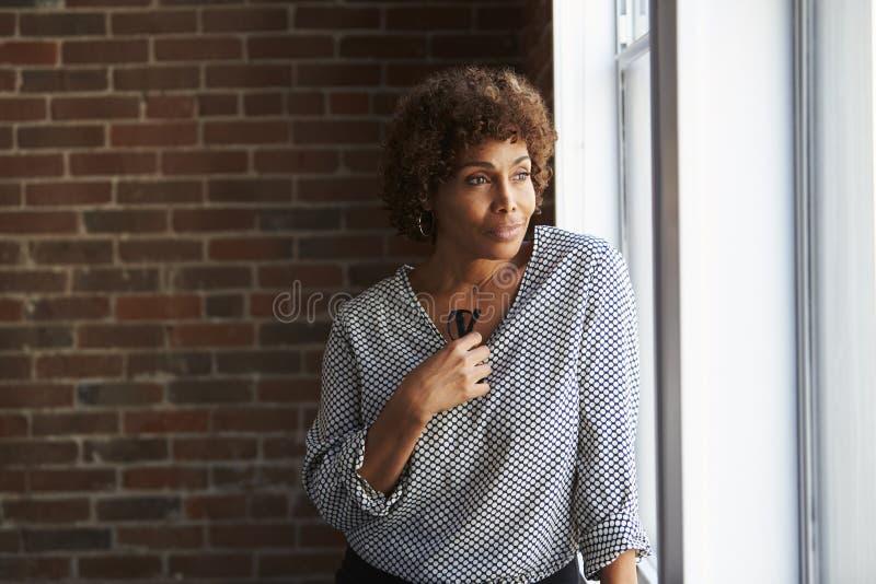看在办公室窗口外面的体贴的成熟女实业家 免版税库存图片