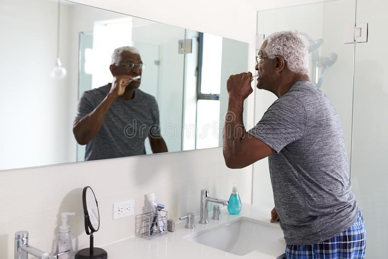 看在卫生间镜子佩带的睡衣的老人反射刷牙 库存图片