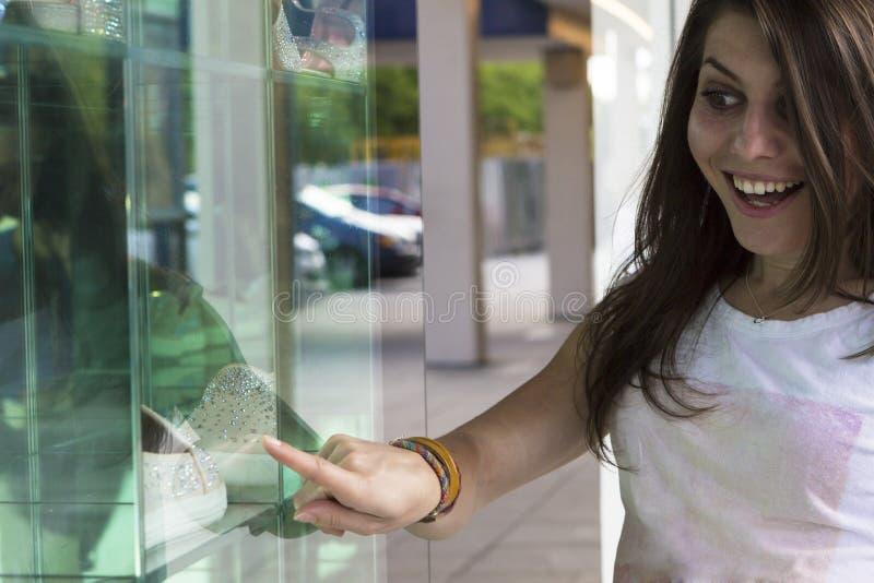 看在商店窗口的愉快的女孩 免版税图库摄影