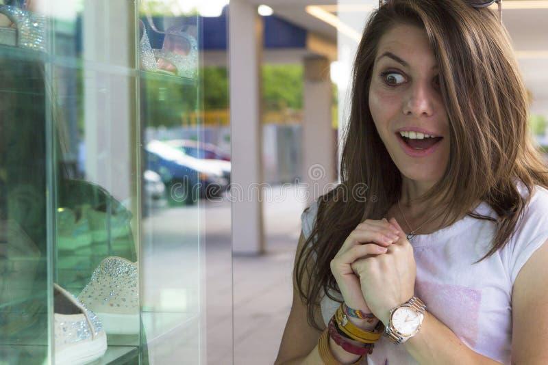 看在商店窗口的愉快的女孩 库存照片