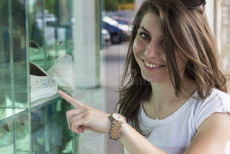 看在商店窗口的愉快的女孩 免版税库存照片
