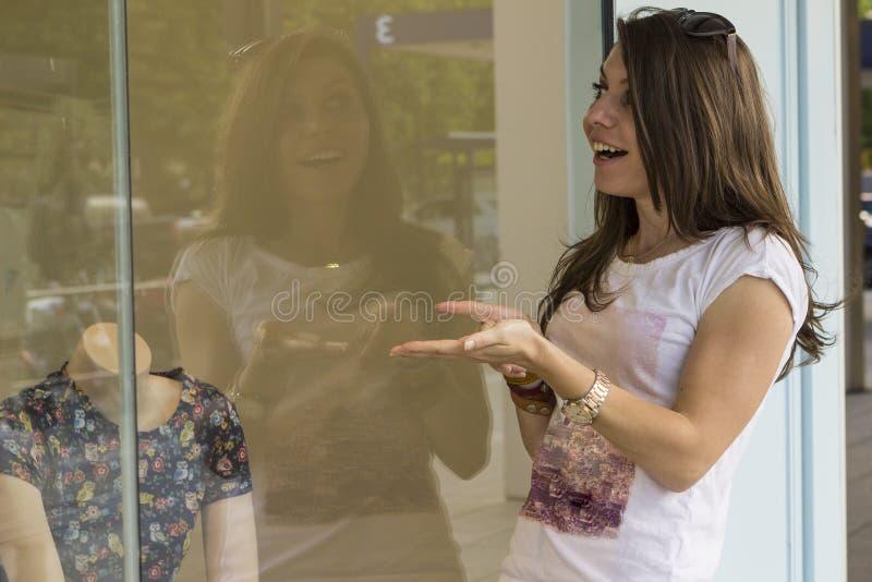 看在商店窗口的愉快的女孩 免版税库存图片