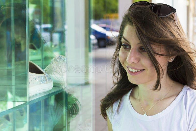 看在商店窗口的愉快的女孩 库存图片