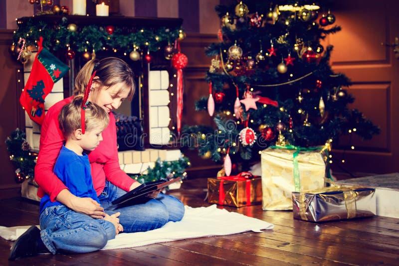看在圣诞节的母亲和儿子触摸板 免版税库存照片