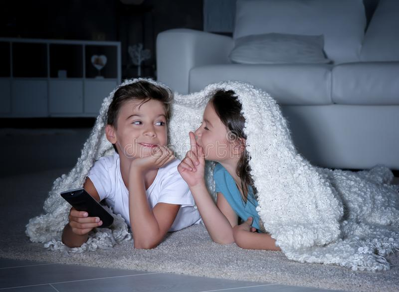 看在地板上的逗人喜爱的孩子电视在晚上 免版税库存图片