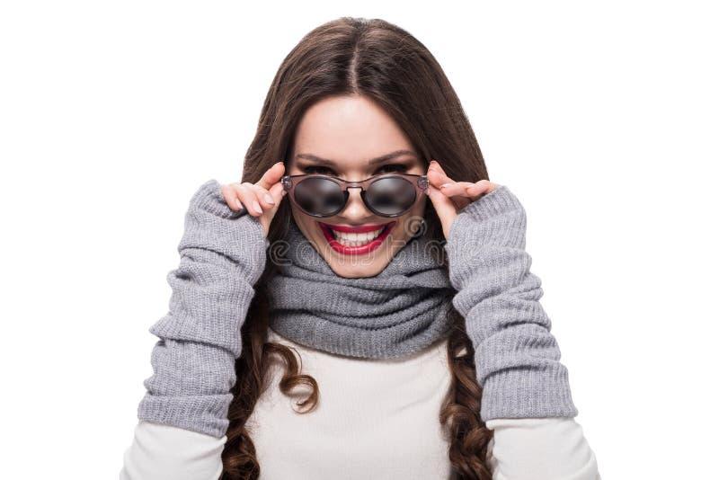 看在太阳镜的冬天服装的年轻微笑的妇女, 图库摄影