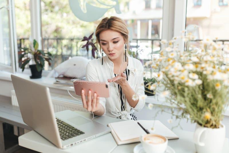 看在她的手机和送亲吻的耳机的少女在咖啡馆 免版税库存图片