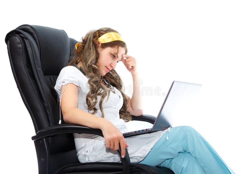 看在她的笔记本的疲乏的护士 免版税库存照片