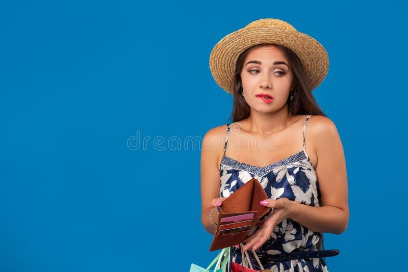 看在她的钱包的不快乐的少妇画象在购物中心,筋疲力尽太多,没有足够的现金,失去的金钱 免版税库存图片